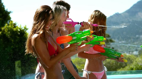 Happy friends doing water gun battle Footage