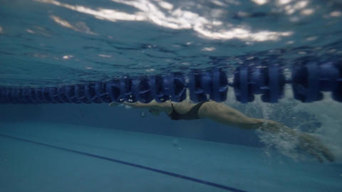 Young woman swimming butterfly style in transparent water pool underwater view Footage