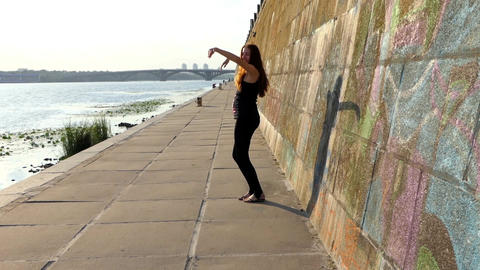 Young Pregnant Woman Dances Disco on a Riverbank With a High Wall in Slo-Mo Footage
