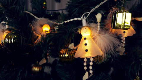 Electrogarlands of white angels are hanging on a Christmas tree. Beautiful cute Footage