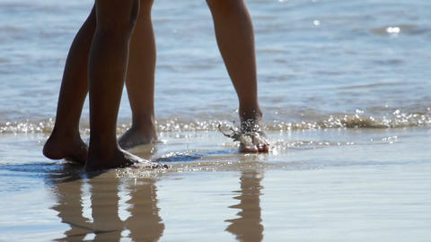 Male and female feet are standing on the sandy beach Footage