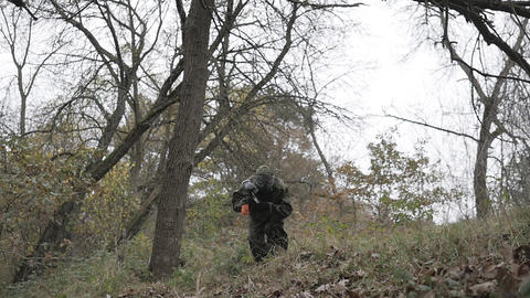 Paintball players storm through the forest in slow motion Footage