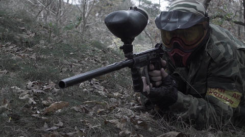 A man lying on the grass shooting from a paintball in slow motion Footage