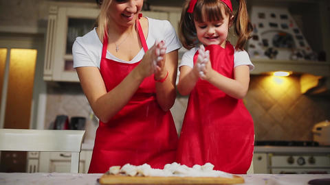 Happy family in the kitchen mom and daughter in the kitchen playing with flour Footage