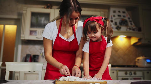 Happy family in the kitchen mom and daughter in the kitchen playing with flour Live Action
