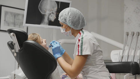 The dentist inspects the braces a little girl and checks the teeth for the Live Action