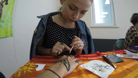 Closeup Girl Draws Orient Patterns with Henna on Client Hand Footage