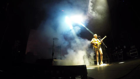 Bottom View front Woman Plays Guitar against Projector Rays Footage