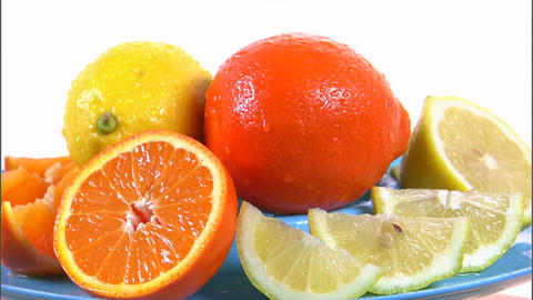 Assorted citrus fruit rotating on white background Live Action