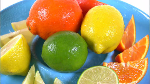 Assorted citrus fruit rotating on white background Footage