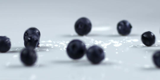 Blueberries dropping onto table Live Action