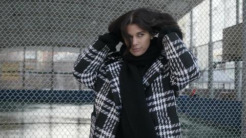 Woman adjusting scarf near net fence Archivo