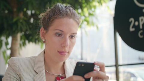 A Young Lady Using a Smartphone in the Cafe Photo