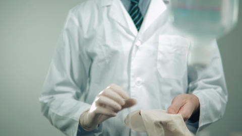 a doctor in a medical gown puts on sterile gloves Footage