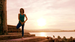 silhouette of woman training yoga gymnastics at sunset Filmmaterial