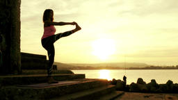 silhouette of woman training yoga gymnastics at sunset Footage