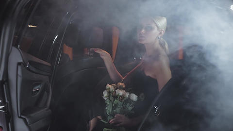 Beautiful blonde with white roses comes out of a black car Bild