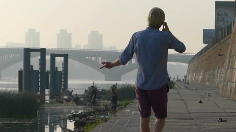 Young Man Speaks by a Mobile, Gesticulates, on the Riverbank in Summer in Slo-Mo Footage