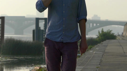 Man Speaks by a Mobile. His Body And Hands Are Seen, on the Riverbank in Slo-Mo Footage