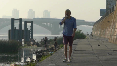Young Man Speaks by a Mobile, Walks, Smiles, on the Riverbank in Slo-Mo Footage