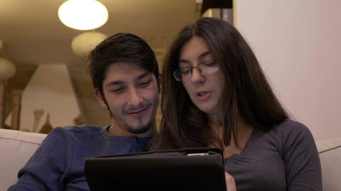 Affectionate happy couple watching video tutorials on tablet pc at home and Footage