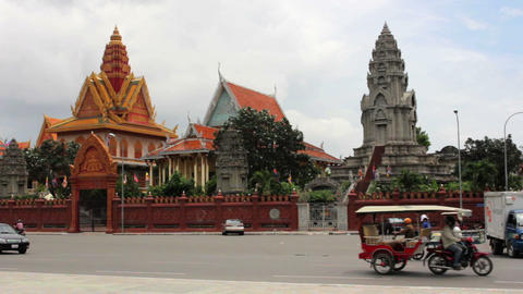 PHNOM PENH - JUNE 2012: regular traffic in front of temple Stock Video Footage