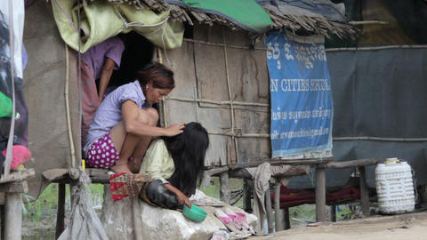 PHNOM PENH SLUMS - JUNE 2012: mother removing louse from... Stock Video Footage