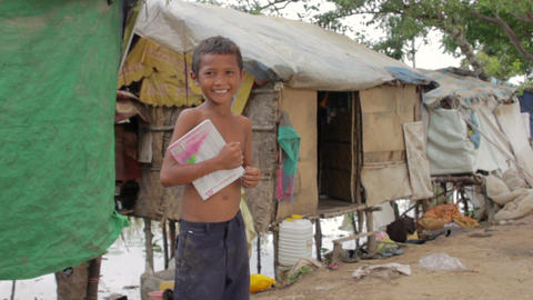 Boy in slum holding book Stock Video Footage