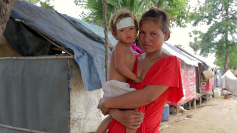Mother holding baby in shanty Stock Video Footage