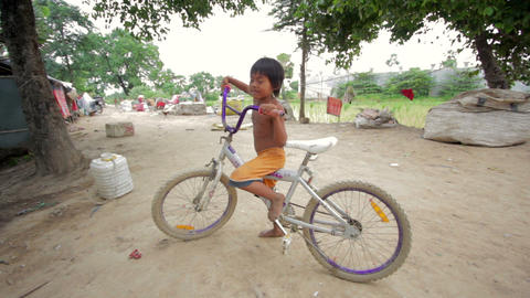 Cambodian boy in slum with bicycle Footage