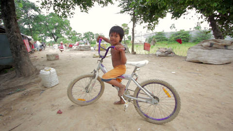 Cambodian boy in slum with bicycle Stock Video Footage
