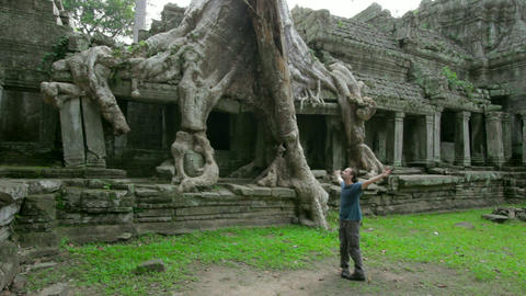 Happy man raised arms in angkor Stock Video Footage