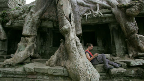 Young man reading book in angkor Stock Video Footage