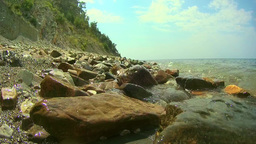 Video - Close-up view of the rocky shore with big waves washing the large boulde Footage