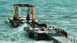 Old breakwater during a heavy storm. Waves splashing into the air through the ho Footage