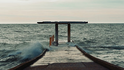 Big waves hit the concrete pier and causing water splashes that flood the surfac Footage