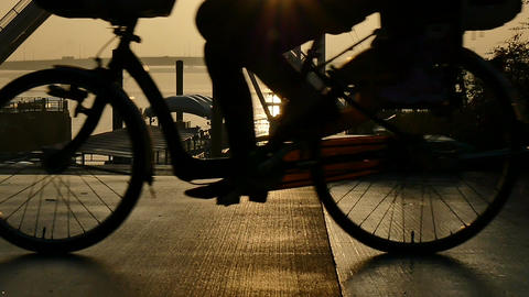 Slow motion view of an anonymous person on a bicycle enjoying the sunset after t ライブ動画