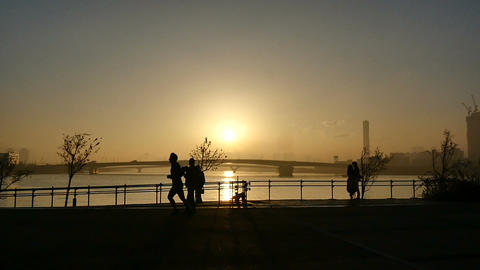 Slow motion view of an anonymous jogger enjoying the sunset after the rain on th ライブ動画