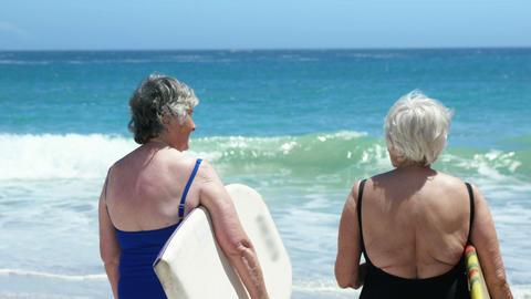 Senior woman holding surfboard Footage