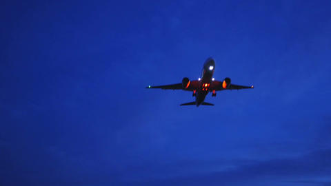 (with sound) A modern jet with red flashing lights approaching landing at twilig Footage