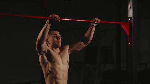 Sports inflated male performs a chin-up lifting above the horizontal bar. Power Footage