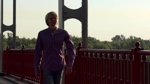 Young Man Walks Along The Handrails of a Bridge at Sunset in Slo-Mo Footage