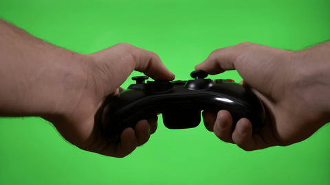 Hands of gamer using game controller to play interactive game on green screen Footage