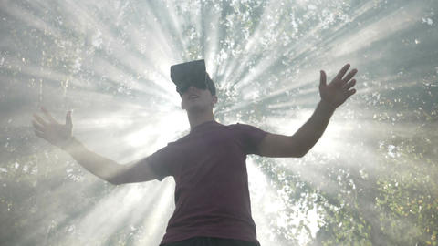 Young man with VR headset gadget immersed into virtual reality covered by light Live Action