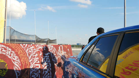 Artists in Black Cap Decorates Blue Car with Patterns Live Action