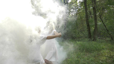 Two happy young women spinning and dancing in the forest through smoke in slow Footage