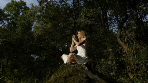 Blonde young woman meditating outdoor in lotus yoga position in the forest Footage