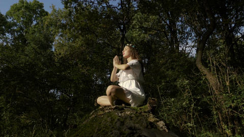 Yogi meditating in the forest in lotus pose in nature Footage