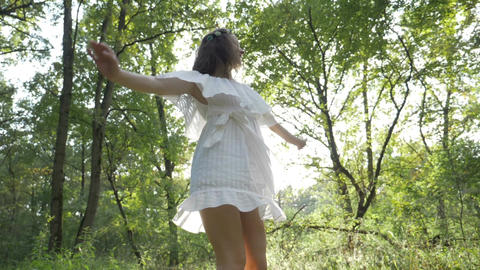 Girl dancing happily in the woods dressed in a angelic white dress Footage