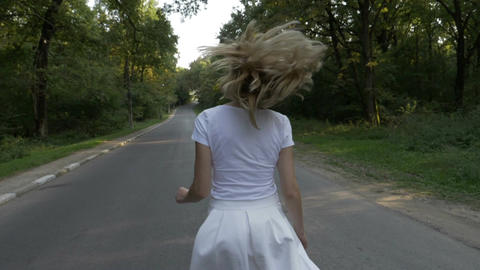 Gorgeous blonde attractive woman running on a forest road and smiling Footage